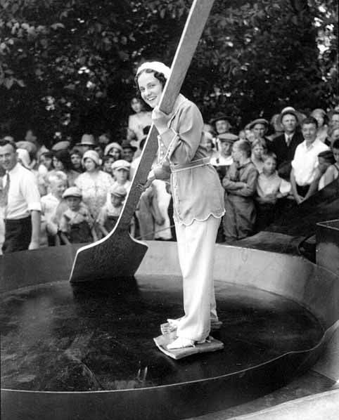 Woman-skating-in-a-skillet-with-slabs-of-bacon-tied-to-her-feet-1